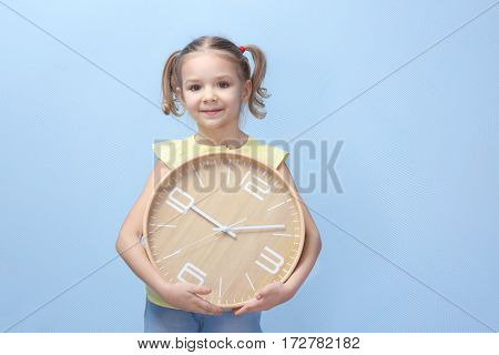 Cute little girl with big clock on color background