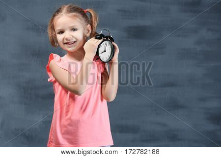 Cute little girl with alarm clock near color wall