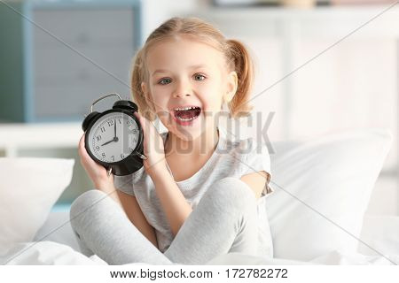 Cute little girl with alarm clock sitting on bed