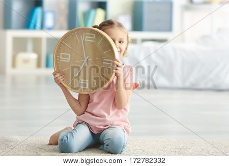 Cute little girl with big clock sitting on floor at home