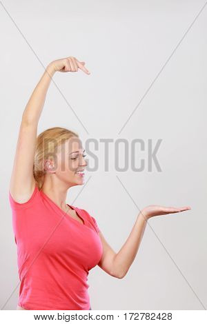 Gestures pointer concept. Happy woman pointing with two hands on right side next to her. Studio shot on light grey background
