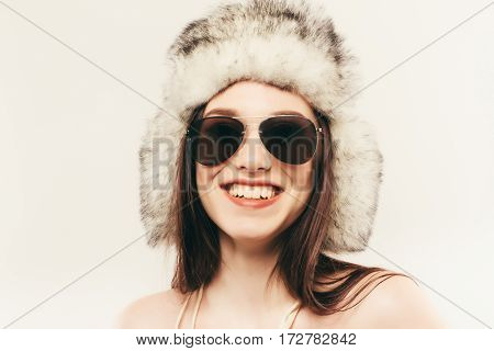 Beautiful And Happy Young Woman Isolated On White And Wearing A Fur Hat And Sunglasses