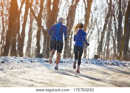 Man and woman in condition runs in forest, back view