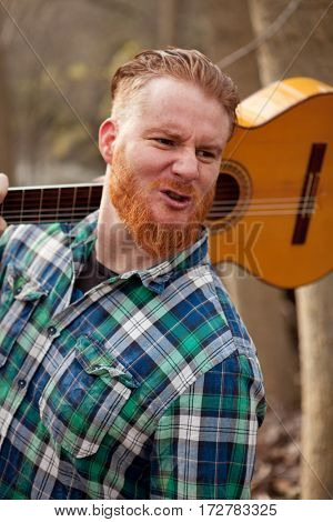 Hipster man with red beard holding a guitar in the field