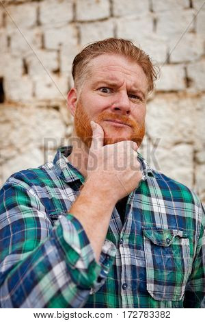 Pensive red haired hipster man with blue plaid shirt in a rural enviroment