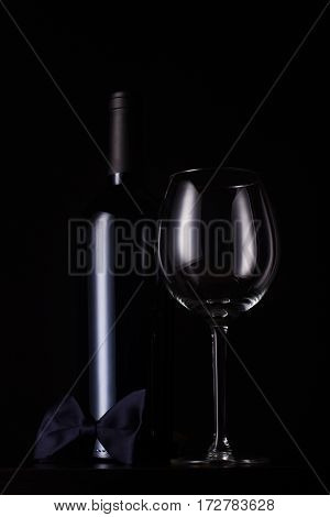 vertical front view of black red wine bottle with cap and no label tall empty glass and a dark bow tie at the base