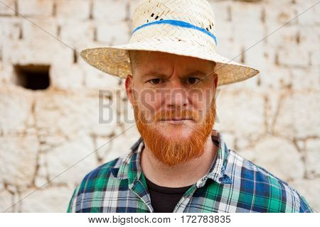 Red haired man with a straw hat in a rural enviroment