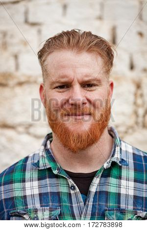 Portrait of red haired hipster man with blue plaid shirt looking at camera