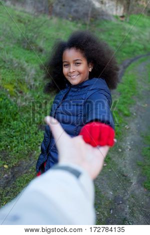 African little girl shakig hands with somebody in the park