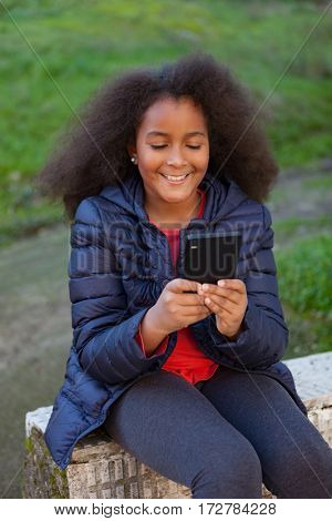 Smiling afro child with a mobile in the park taking a photo himself