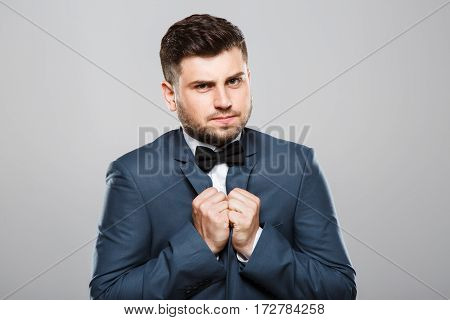 Stylish young man in suit with bow. Looking seriously at camera. Jacket, bow, official outlook. Waist up, studio, indoors