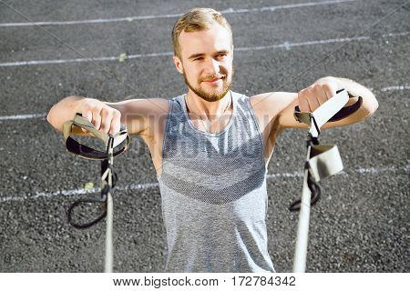 Young man wearing dark sport T-shirt doing exercises with training loop equipment at stadium background, portrait.