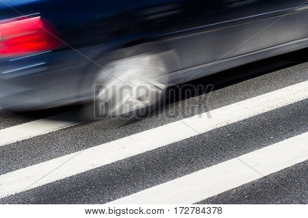 Horizontal side view of a black car with motion blur speeding over a pedestrian crossing