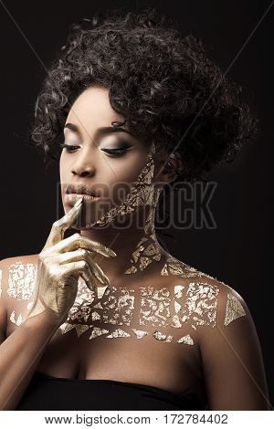 Beautiful Afro-American girl with curly hair in black dress. Make-up, hairdo. Covered with golden patterns. Looking down, finger touching mouth. Waist up, indoors, studio