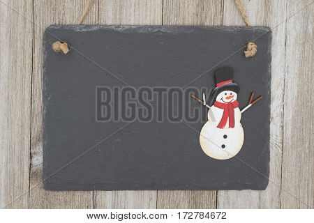 Old fashion Christmas hanging chalkboard background A retro chalkboard with a snowman hanging on weathered wood background with copy space for your message