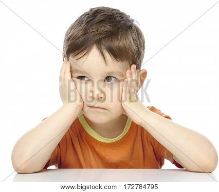 Portrait of a cute little boy sitting at table supporting his head with hands, isolated over white