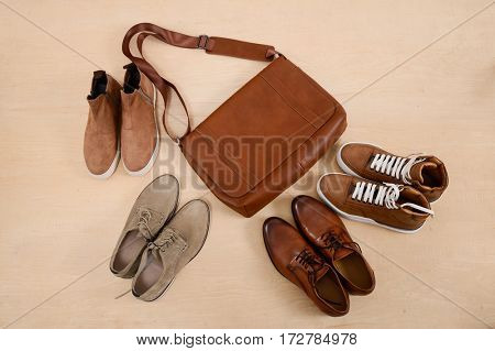 Men's boots , leather brown shoes ,handbag on wooden background