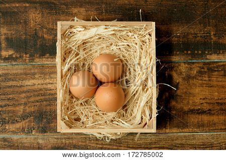 Eggs on straw placed on a wooden table