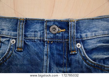 Details from blue jeans-wooden background