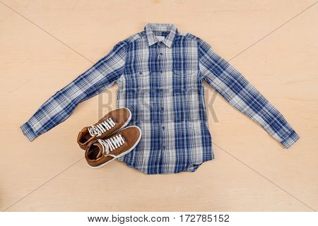 Mans shoes and shirt on wood background