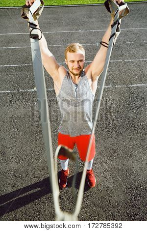Sportive man wearing dark sport T-shirt doing exercises with training loop equipment at stadium background, portrait, arms training.