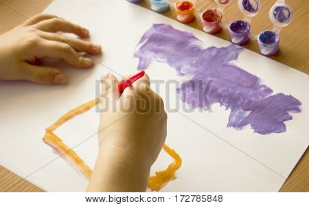 child draws on a white sheet with colored paints the child learns to paint