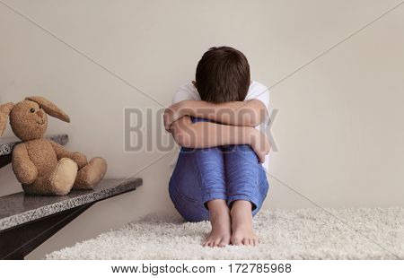 Sad little boy sitting beside stairs