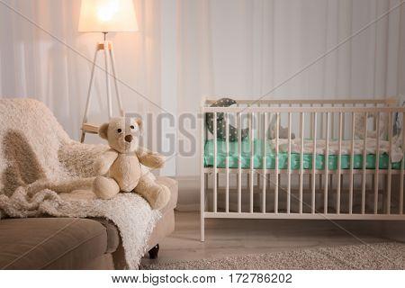 Beautiful teddy bear sitting on sofa in baby room