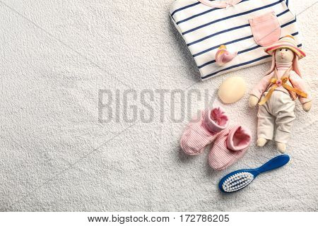Baby clothes and necessities on beige towel background