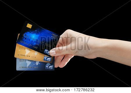 Hand holding credit cards on black background