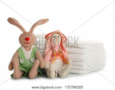 Stack of baby diapers and toys on white background