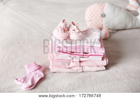 Set of baby clothes and toy on bed