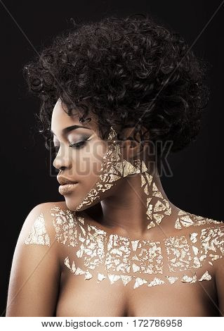 Portrait of beautiful Afro-American girl with dark curly hair. Make-up, hairdo, gold. Covered with golden patterns. Closed eyes. Head and shoulders, profile, indoors, studio