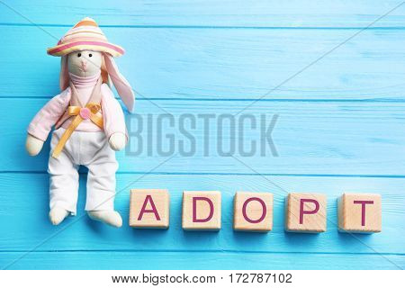 Bunny toy and cubes with word ADOPT on wooden background
