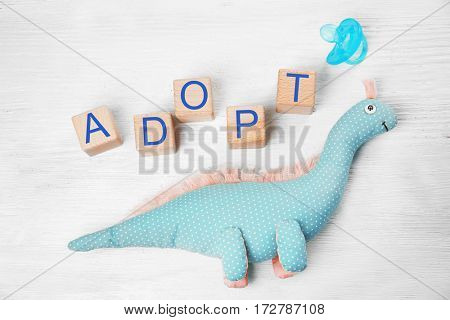 Cubes with word ADOPT, dinosaur toy and passifier on light wooden background