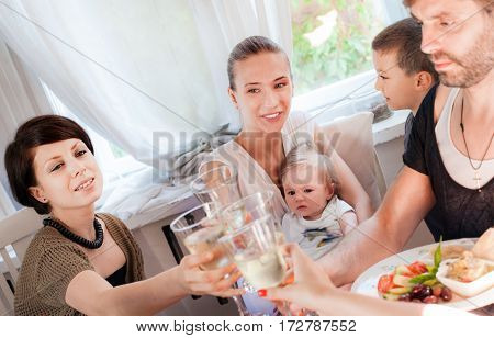 A group of friends with a baby and a young boy are having fun in a restaurant.