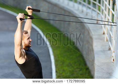 Profile of man training with expander hooked on fence. Muscular sportsman pulling expander to himself, hands up. Sport, outdoors, stadium, waist up