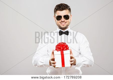 Smiling man with black hair and beard wearing white shirt with bowtie and sunglasses at gray studio background and holding present, portrait, copy space.
