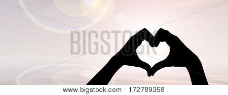 Concept or conceptual heart shape 3D illustration or symbol of human or woman and man hand silhouette over sky, sea at sunset background banner
