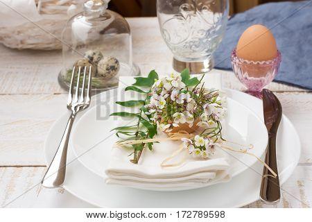 Easter decoration table setting white plates napkin white flowers in eggshell quail eggs green leaves basket outdoors kinfolk
