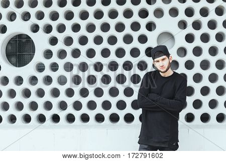 Young man standing near wall. Boy in torn jeans, black T-shirt and black cap. Looking at camera, hands crossed. Outside