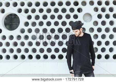 Young man standing near wall. Boy in torn jeans, black T-shirt and black cap. Looking down. Outside
