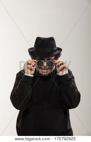 Guy with a black hat and stylish glasses, studio portrait