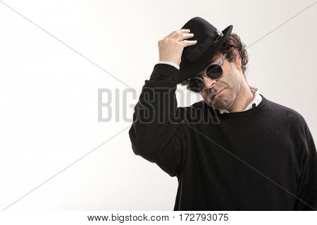Guy takes off his black hat, studio portrait