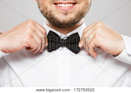 Close up portrait of black bowtie at man's shirt, smiling and touching bowtie.