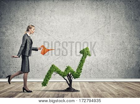 Young attractive businesswoman watering arrow shaped plant in ground with watering can.