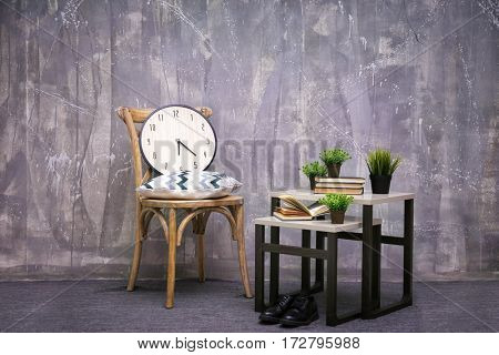 Modern interior design with wooden chair and little table on grey background