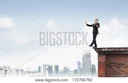 Businessman with blindfold on eyes walking off building top.