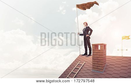 Businessman in safety hardhat standing on house roof and holding red flag. Mixed media.