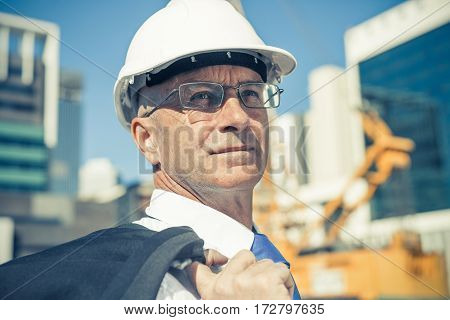 Confident construction engineer in safety hardhat and with jacket on shoulder.